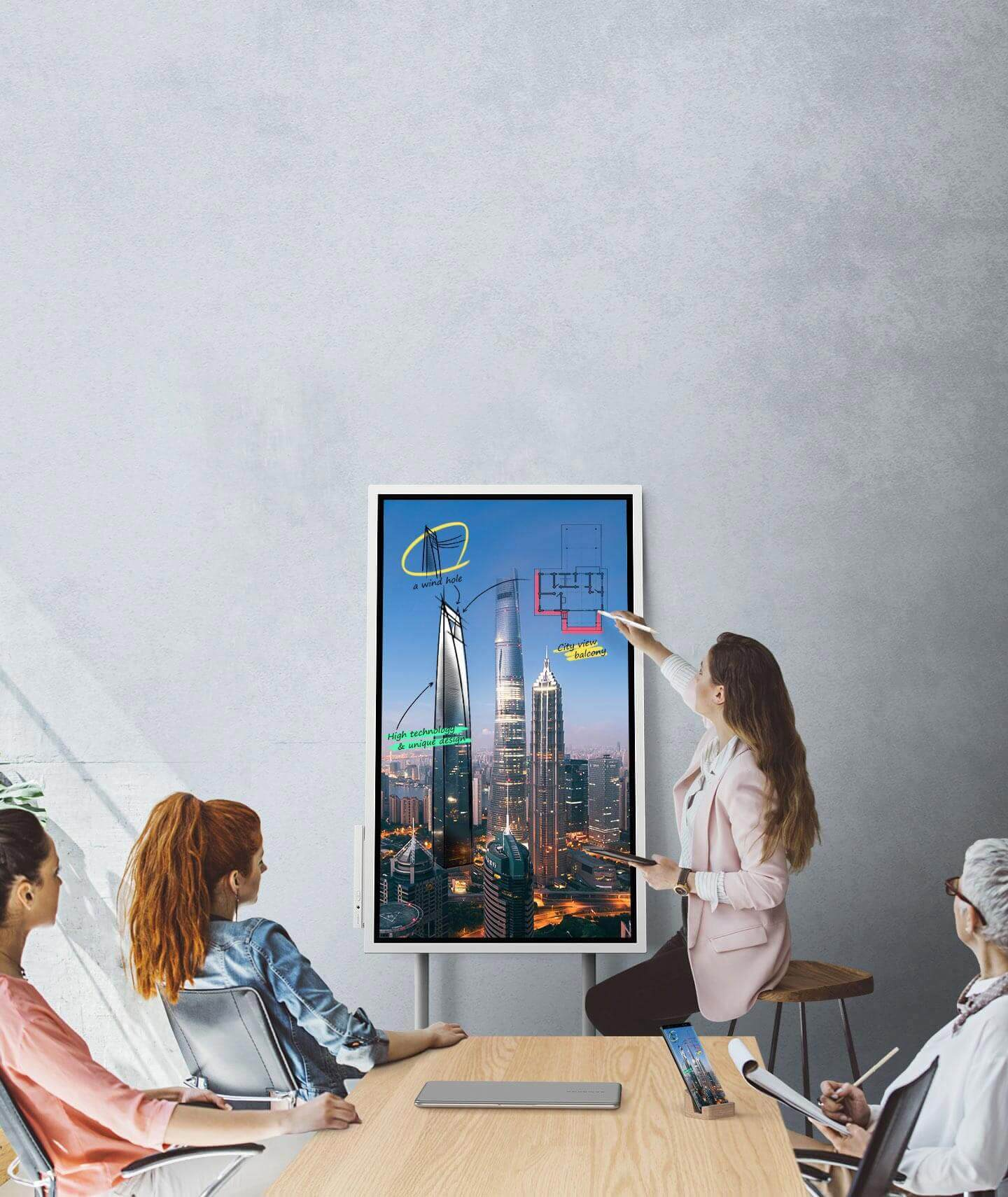 An image showing four people in a meeting where a Samsung Flip device and a smartphone are connected, showing the same images. They are looking at the Samsung Flip's screen positioned in Portait mode and two of them are taking notes.