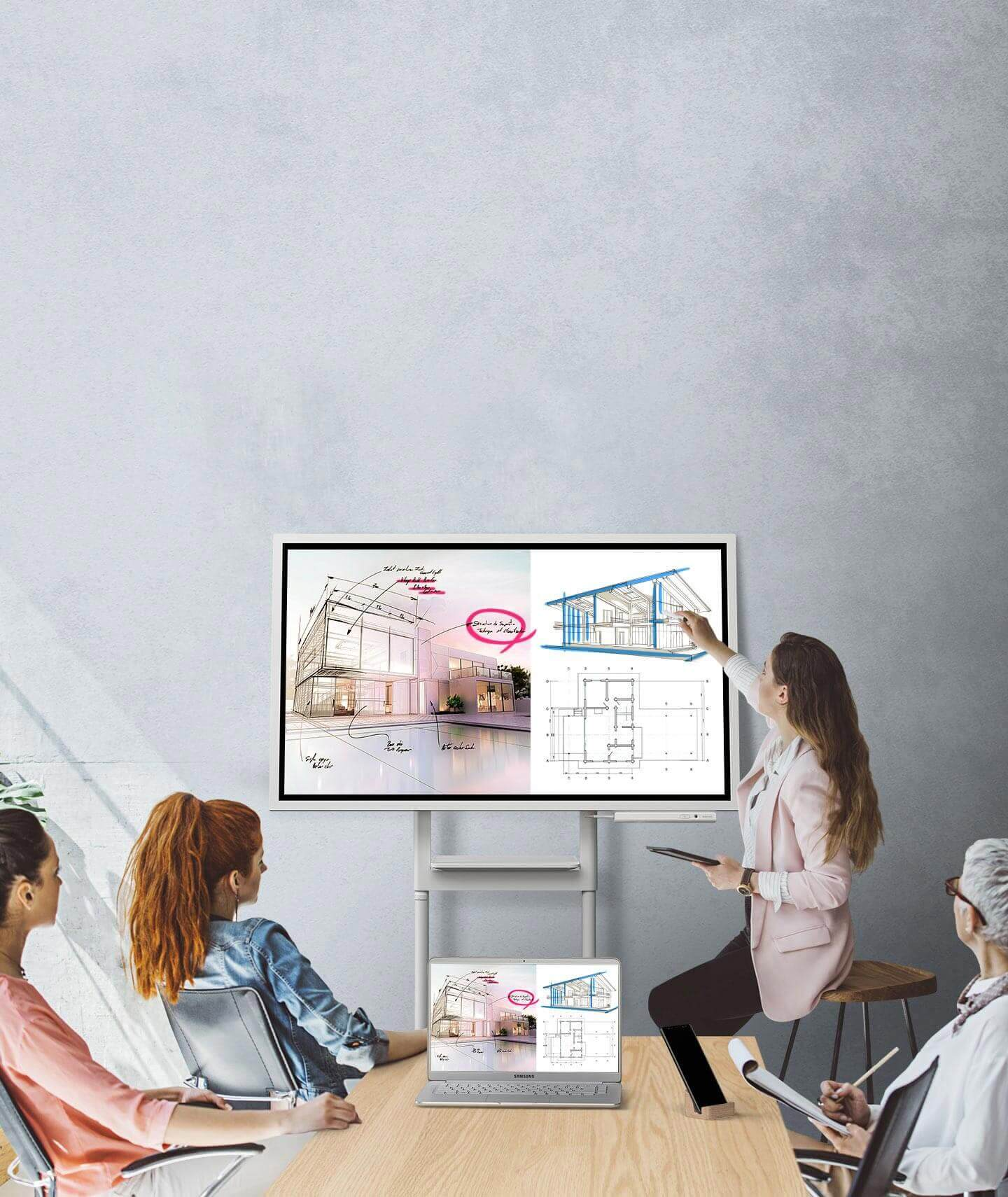 An image showing four people in a meeting where a Samsung Flip device and a pc are connected, showing the same images. They are looking at the Samsung Flip's screen positioned in Landscape mode and two of them are taking notes.